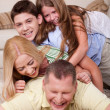 Happy family of four having fun in bed — Stock Photo #3491069