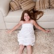 Beautiful little girl sitting on carpet — Stock Photo #3491079