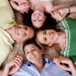 Happy family of four lying on the carpet — Stock Photo #3491081