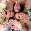 Happy family of four lying on the carpet - Stock Photo
