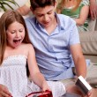 Kids opening christmas gifts with parents in the background — Stockfoto