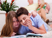 Kids studying with family in the background — Stock Photo