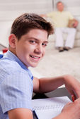 Young boy in focus, studying and smiling at camera — ストック写真