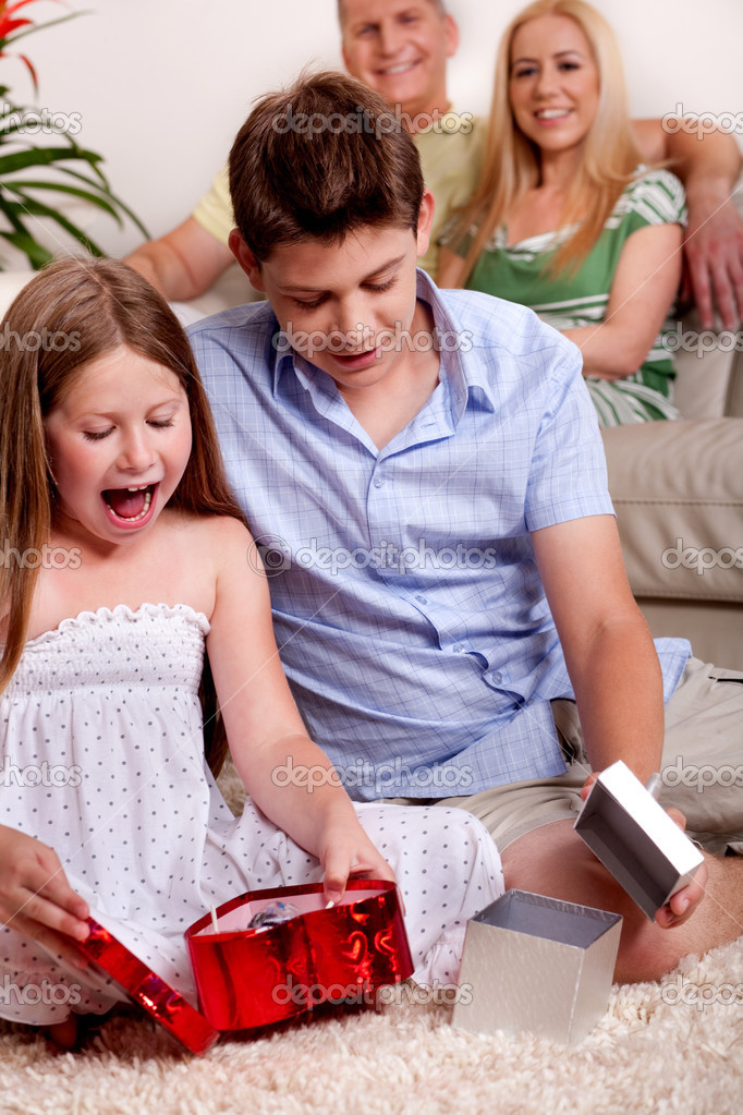 Brother and sister busy in opening christmas gifts with parents in the background — Stock Photo #3491113