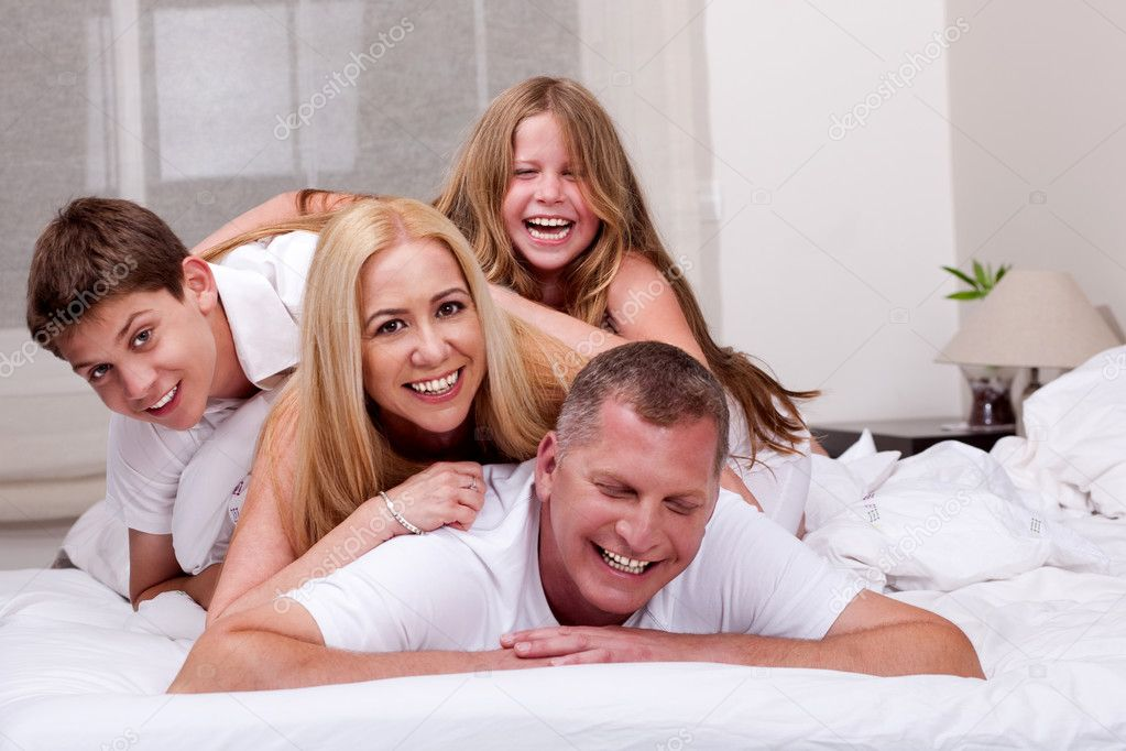 Joyful family of four having fun as they pile up on each other — Stock Photo #3491170