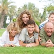 Multi-generation family relaxing in park — Stock Photo
