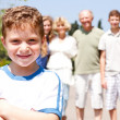 Young cute boy in focus with family in the background - Stock Photo
