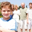 Young cute boy in focus with family in the background — Stock Photo
