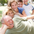 Multi-generation family realxing in park — Stock Photo