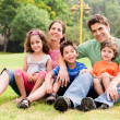 Stock Photo: Family seated in park and smiling at camera
