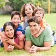 Happy family lying in the park — Stock Photo