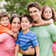 Caucasian parents piggyback their children — Stock Photo