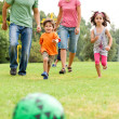 Family playing football in the park — Stock Photo