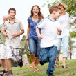 Stock Photo: Family chasing young kid in the park