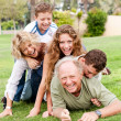 Family piling up on dad — Stock Photo