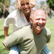 Senior man giving piggy ride to her wife — Stock Photo