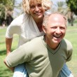 Senior man giving piggy ride to her wife — Stock Photo #3606076