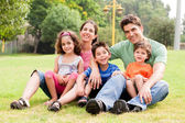 Family seated in park and smiling at camera — Stock Photo