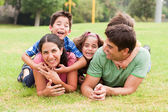 Playful family lying outdoors and smiling — Stock Photo