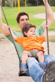 Father enjoying swing ride with his son — Stock Photo