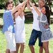 Stock Photo: Group of happy friends with raised arms
