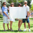 Teens with white billboard standing in park — 图库照片