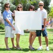 Teens with white billboard standing in park — Foto de Stock