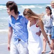 Romantic couples walking down the beach — 图库照片