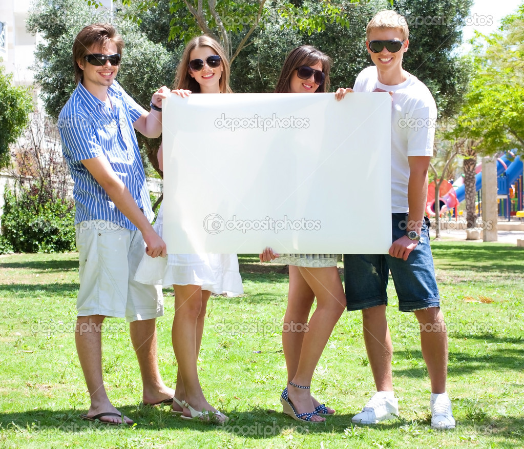 Teens with white billboard standing in park and advertising — Stock Photo #3676982