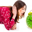 Lady looking at alarm clock - Stock Photo