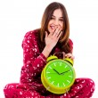 Teenager sitting with alarm clock - Stock Photo