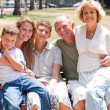 Happy family sitting on park bench — Stock Photo
