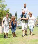 Happy family running towards camera — Stock Photo