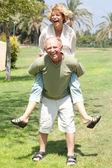 Image of Senior man giving woman piggyback ride — Stock Photo