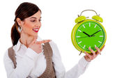 Lady pointing at alarm clock — Stockfoto