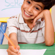 Foto Stock: Portrait of cheerful boy writing notes