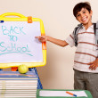 Stock Photo: Smiling school boy pointing at white board