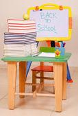 Schoolboeken en apple op bureau met sketchboard — Stockfoto