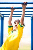Smart kid playing on jungle gym — Stock Photo