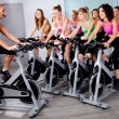 Foto Stock: Group of doing exercise on a bike
