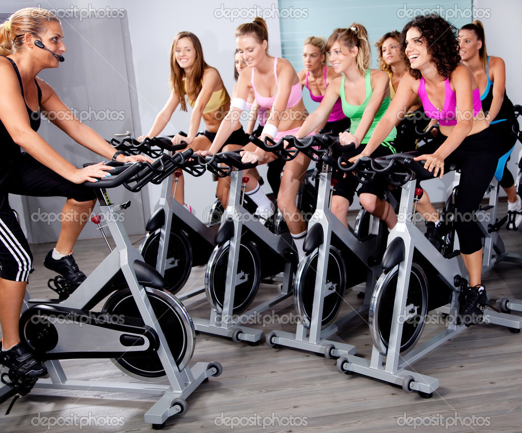 Image of group of doing exercise on a bike in a gym — Stock Photo #3900879