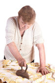 The old woman irons a cloth — Stock Photo