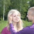 Young man attaches to hair  girl a flowe — Stock Photo