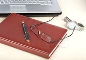 The laptop an organizer a pen and clock — Stock Photo