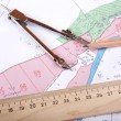 Stock Photo: Topographic map of district with measuring instrument and pen