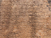 Ancient inscriptions on stone wall — Stockfoto