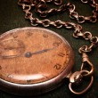 Old clock with chain lying on rough green surface — Stock Photo #3757370
