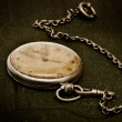 Old clock with chain lying on rough green surface — Stock Photo