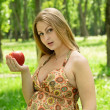 Pregnant woman with apple in the park — Stock Photo