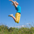 Woman jumping on blue sky — Stock Photo